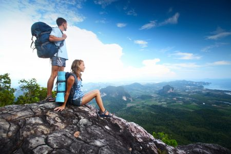 Two hikers with backpacks standing on top of a mountain and looking to a valley